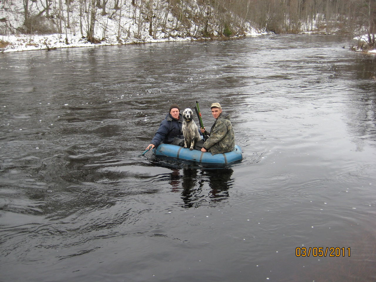 охотник плывя по озеру на легкой надувной лодке